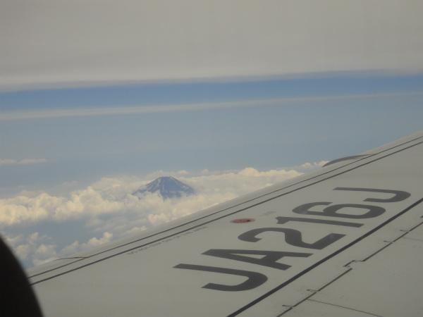 飛行機の窓からまだ雪の残る富士山の頂を見る